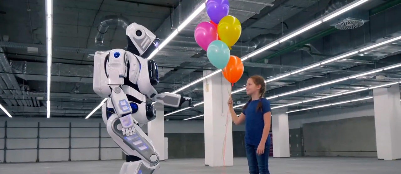 Girl with balloons in her hand playing with a robot | enel.it